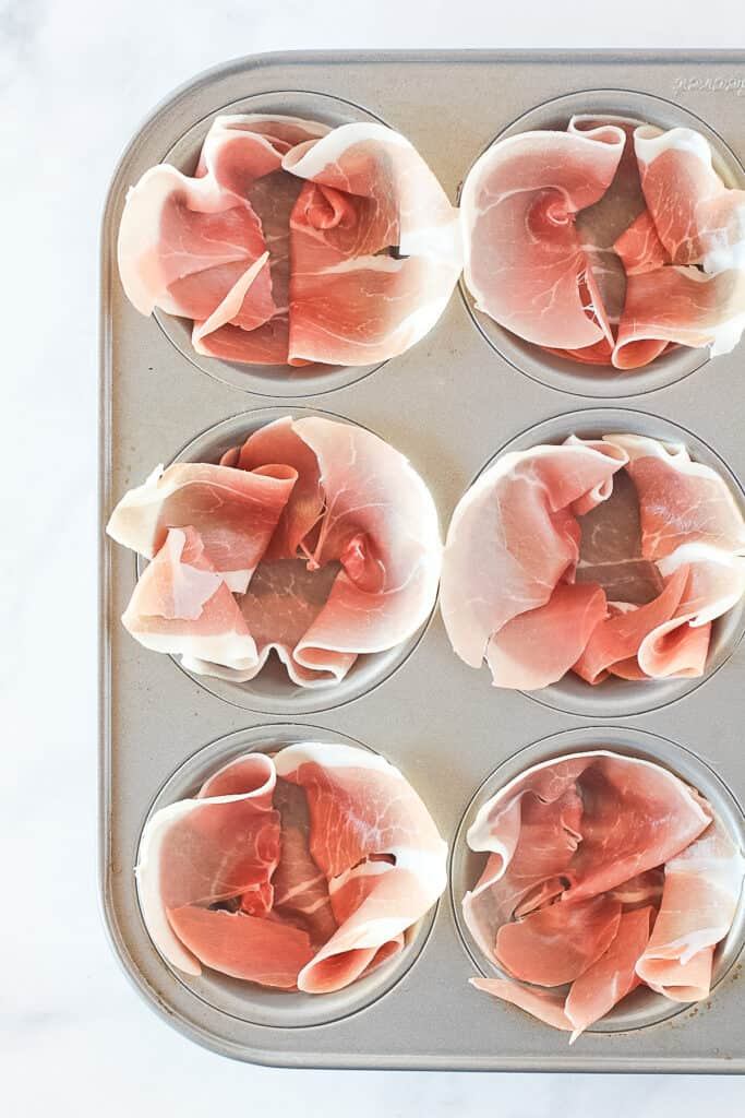 Muffin tin lined with prosciutto in the process of making egg muffins.