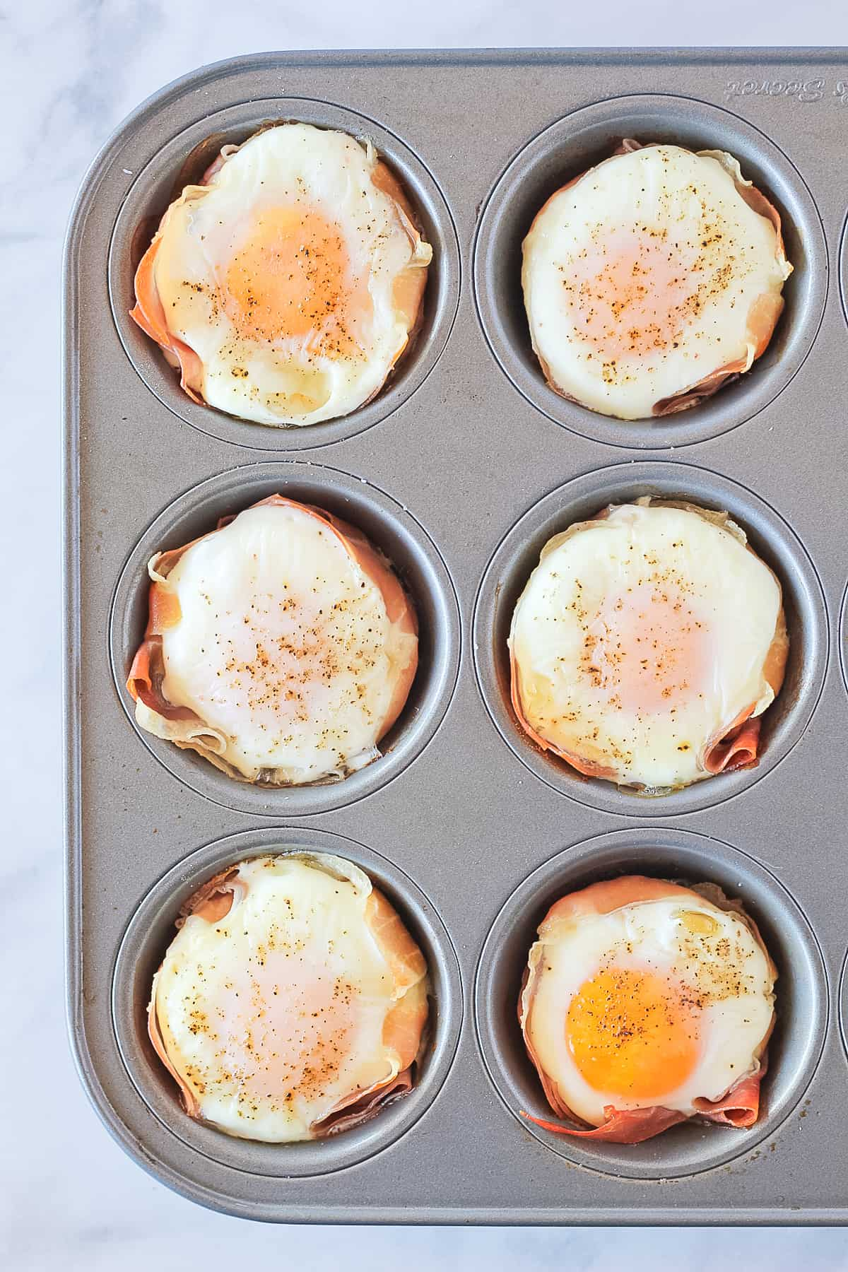 Muffin pan with 6 cooked keto egg muffins.