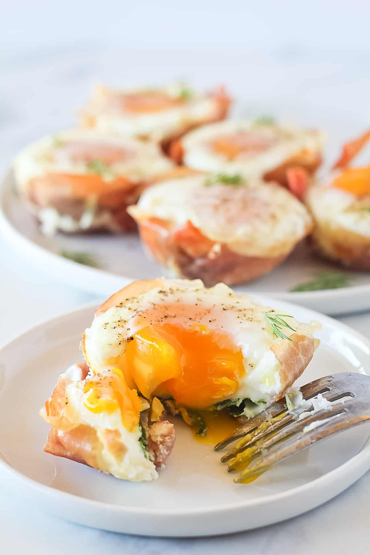 One prosciutto, spinach egg cup being cut into with a fork on a white plate and more egg muffins in the background.
