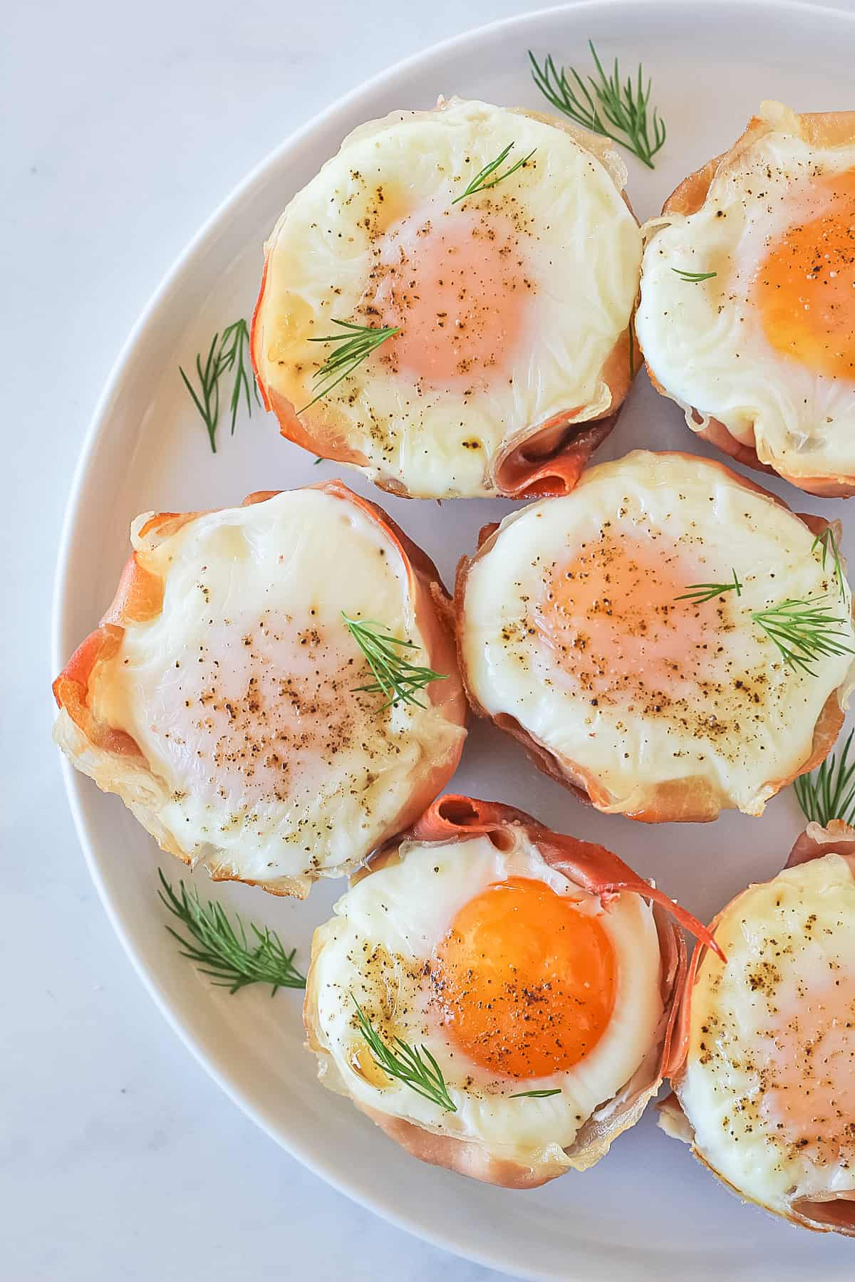 White plate with six prosciutto, spinach egg cups garnished with fresh dill.