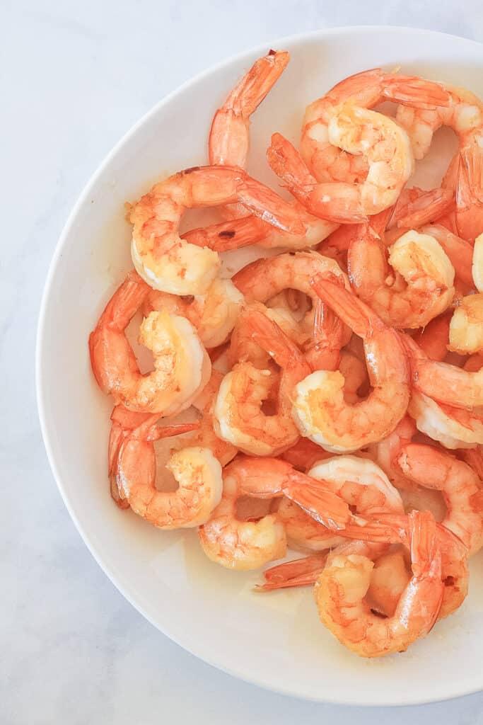 White plate full of cooked shrimp.
