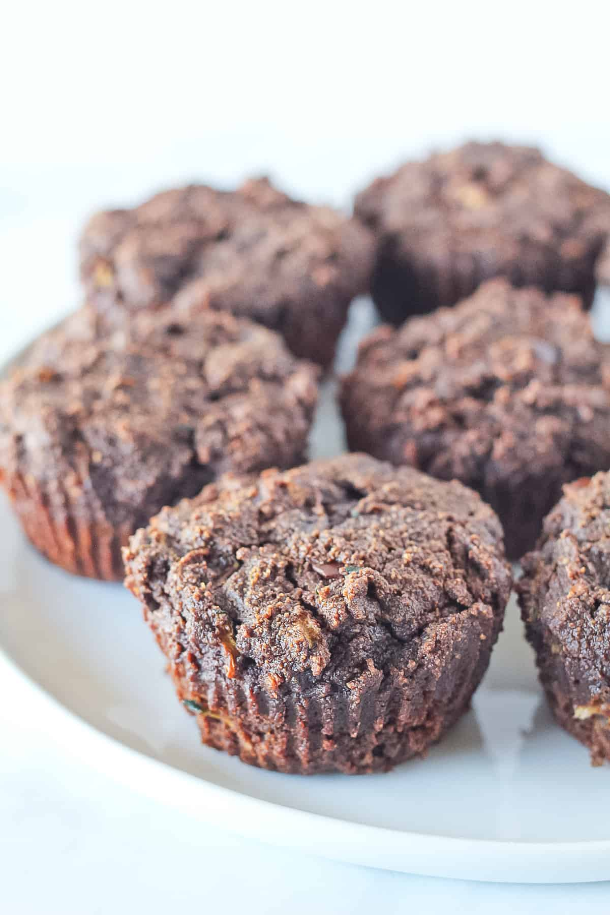 White plate of chocolate zucchini muffins.