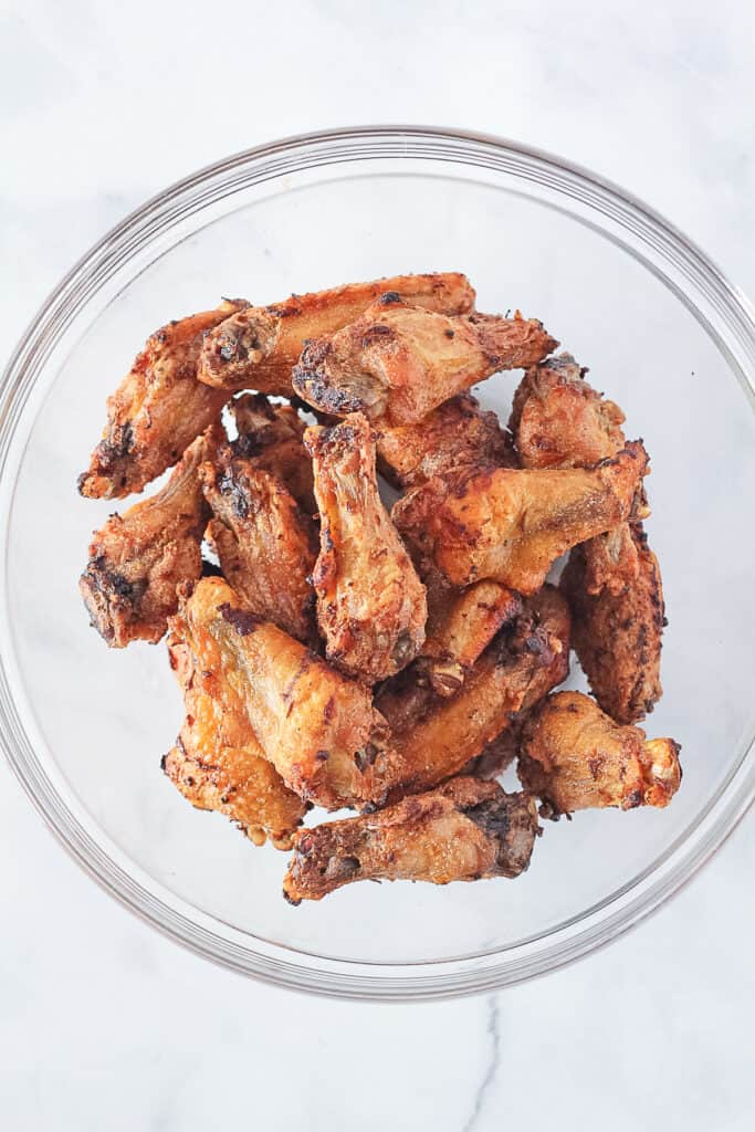 Baked chicken wings in a glass mixing bowl.