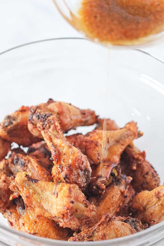 Baked chicken wings in a glass mixing bowl with lemon pepper sauce being poured over top.
