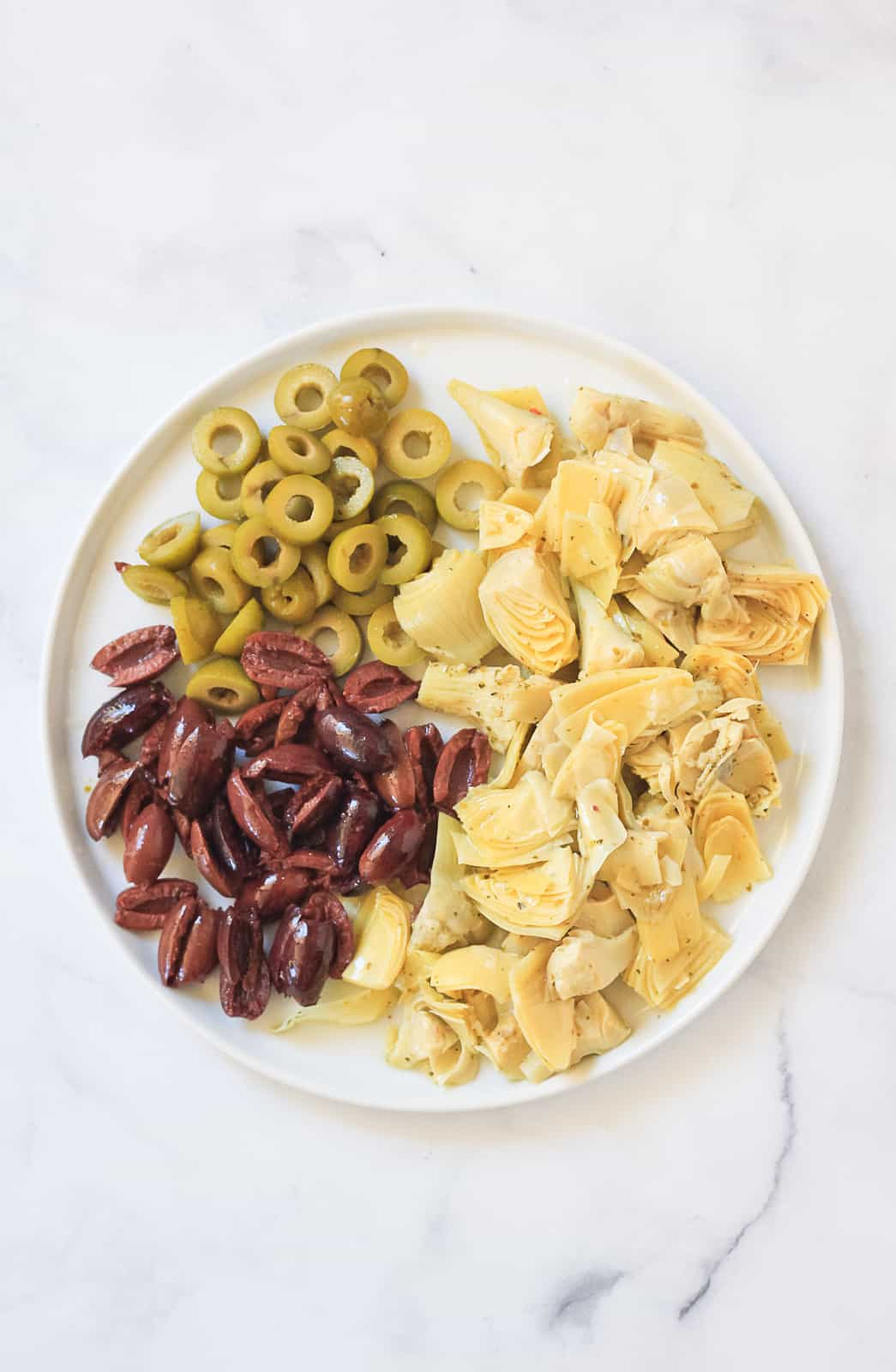 White plate full of cut green olives, khalamata olives and marinated artichoke hearts for a summer pasta.