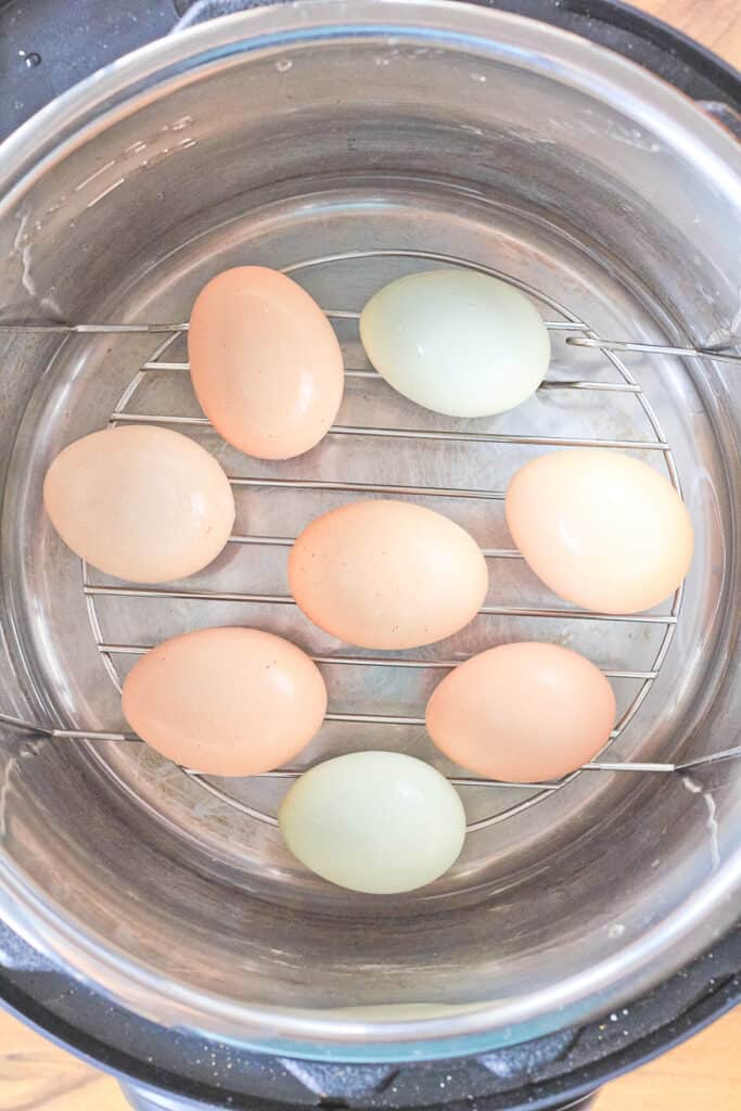 Top view into the Instant Pot of eggs on top of the metal trivet with water in the bottom of the pot.