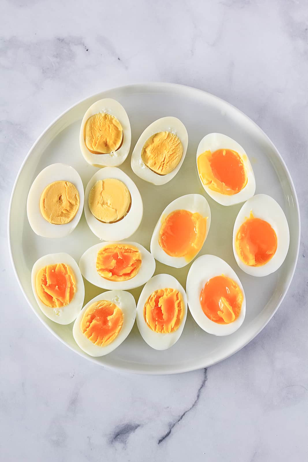Three styles of Instant Pot Hard Boiled Eggs on a white plate including hard boiled, soft boiled and jammy / runny yolk.