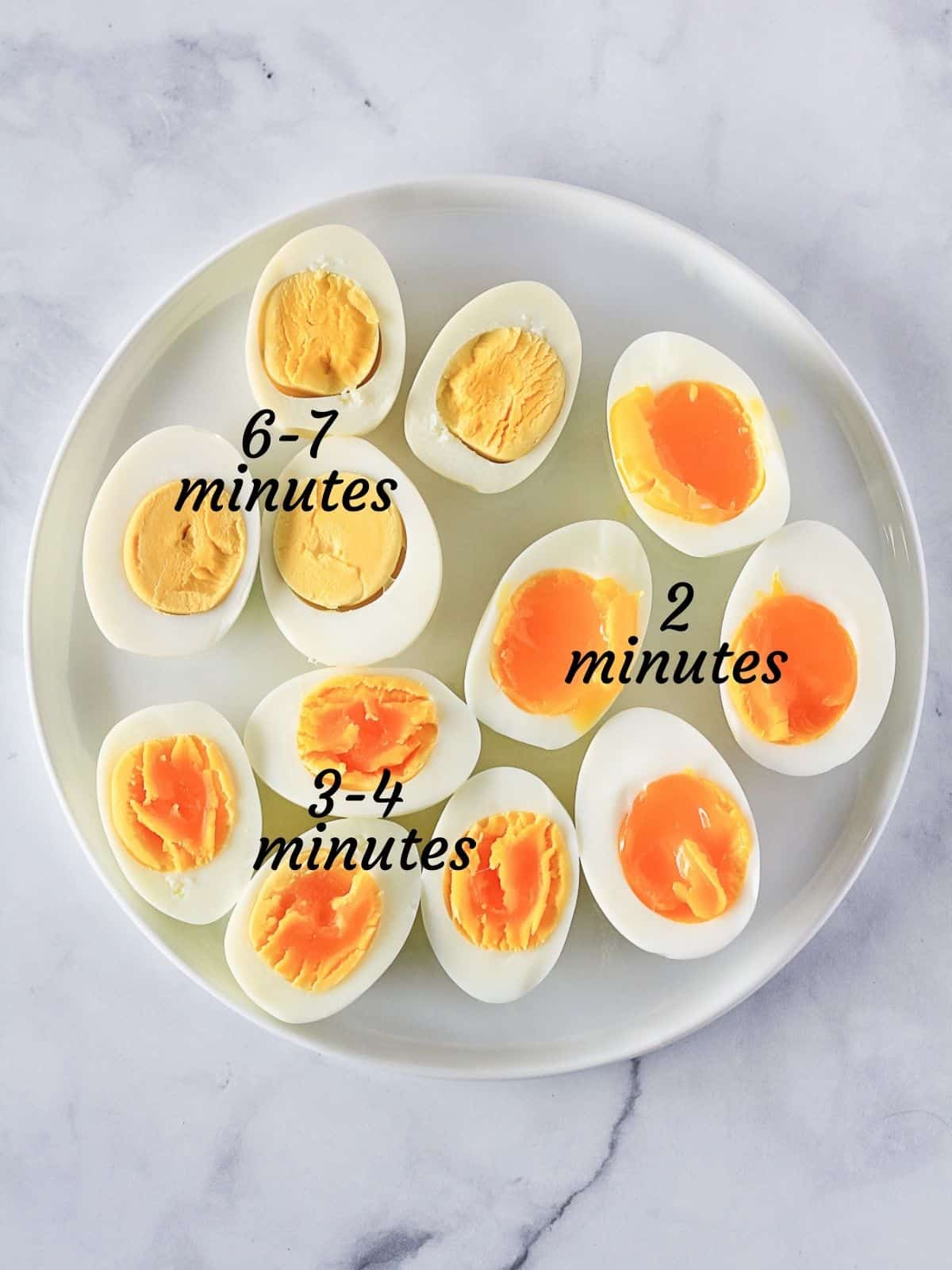 Three kinds of Instant Pot Hard Boiled Eggs on a crate and barrel white plate with black cooking times listed over top the eggs.