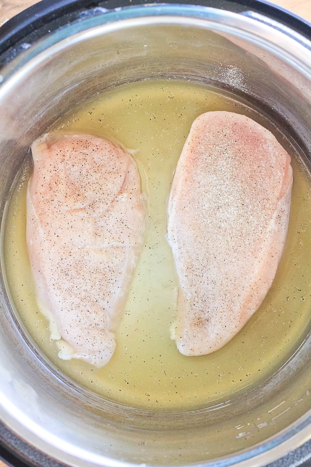 Two raw chicken breasts in broth/stock inside the instant pot.