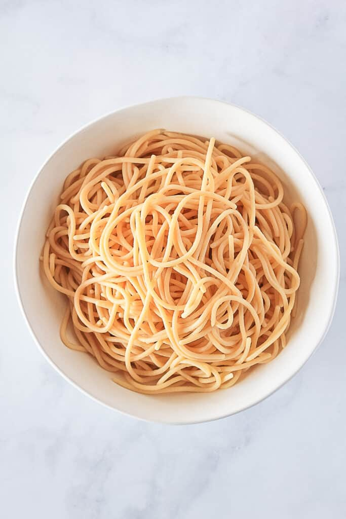 White bowl full of cooked gluten free spaghetti noodles.
