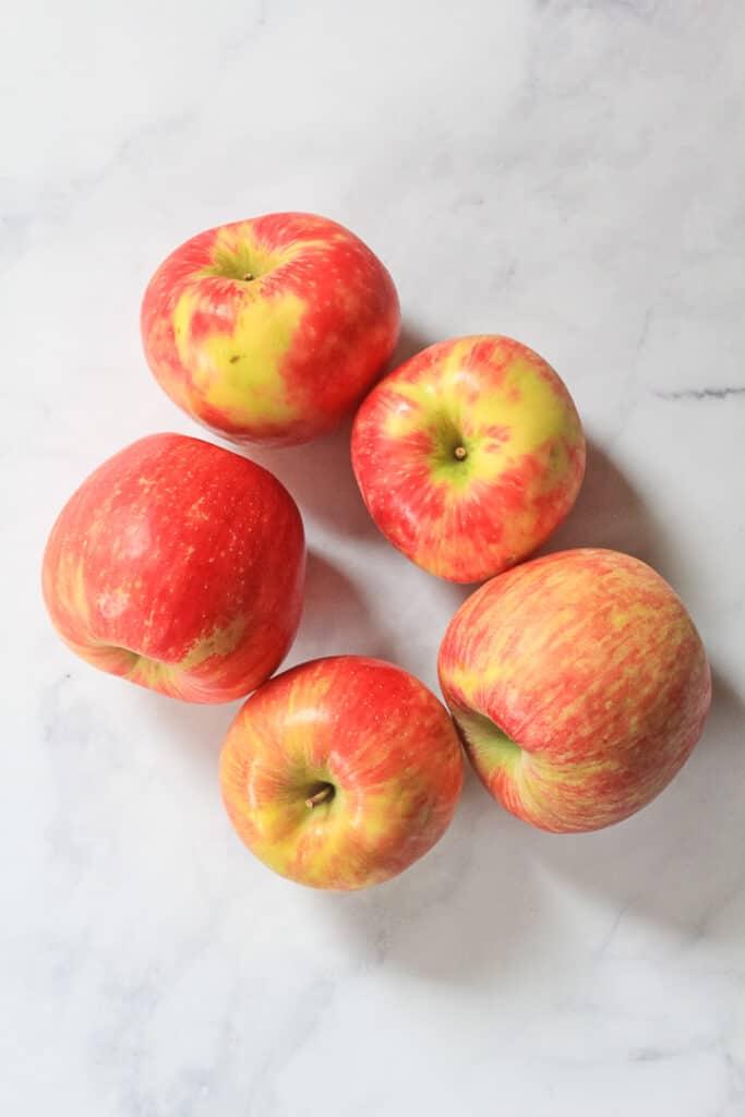Five large whole honeycrisp apples.