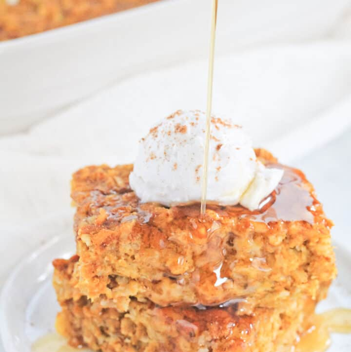 Two square of pumpkin baked oatmeal stacked on a white plate topped with a dollop of coconut cream, sprinkle of pumpkin pie spice and drizzle of maple syrup.