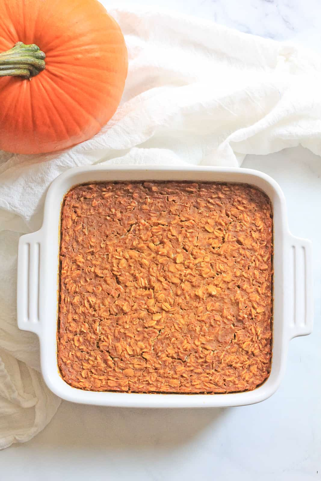 White square baking dish full of pumpkin oatmeal bake with a white towel and orange pie pumpkin.