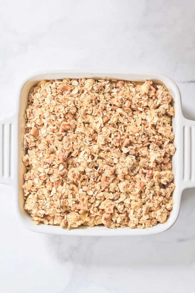 Overhead view of a white square baking dish filled with apple crisp ready for the oven.