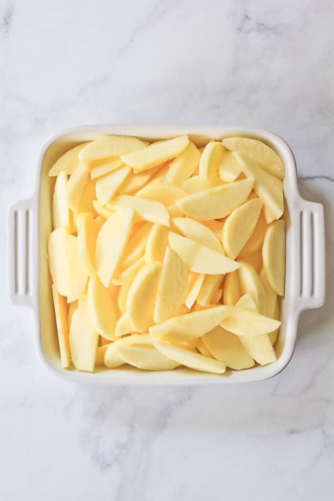 Sliced honeycrisp apples in a square white baking dish.