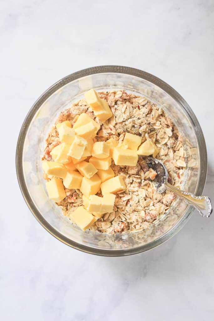 Apple crisp oat topping in a glass mixing bowl with cubes of butter ready to be mixed in.