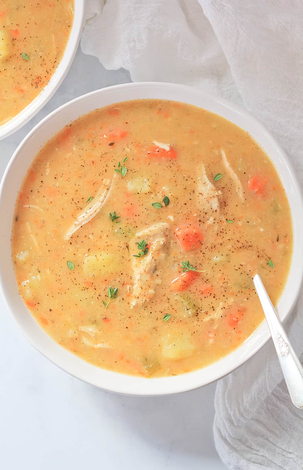 White bowl full of Chicken Pot Pie Soup with a silver spoon.