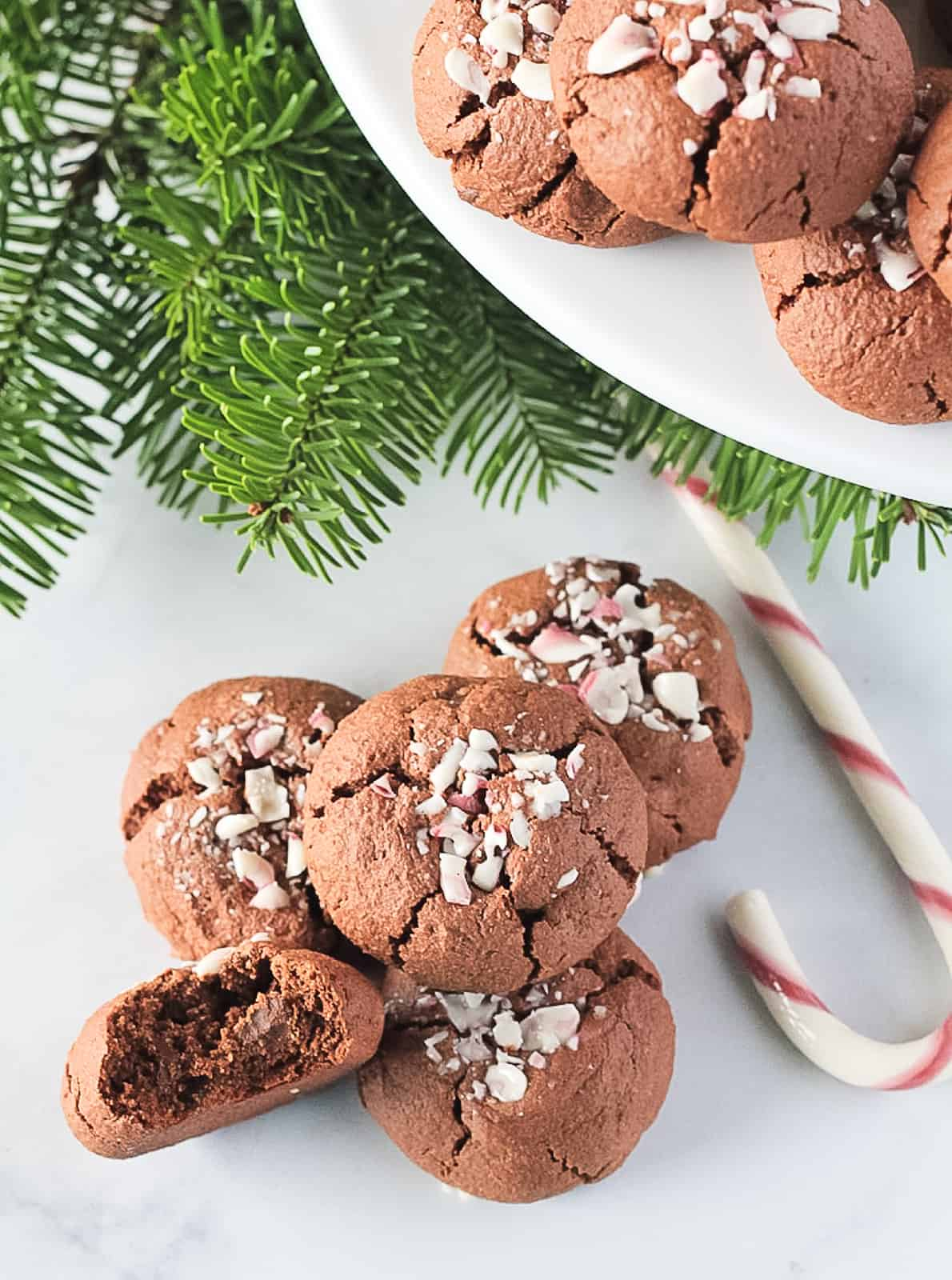 White plate and stack of double chocolate cookies with candy cane topping. Pine branch and bite out of cookie.