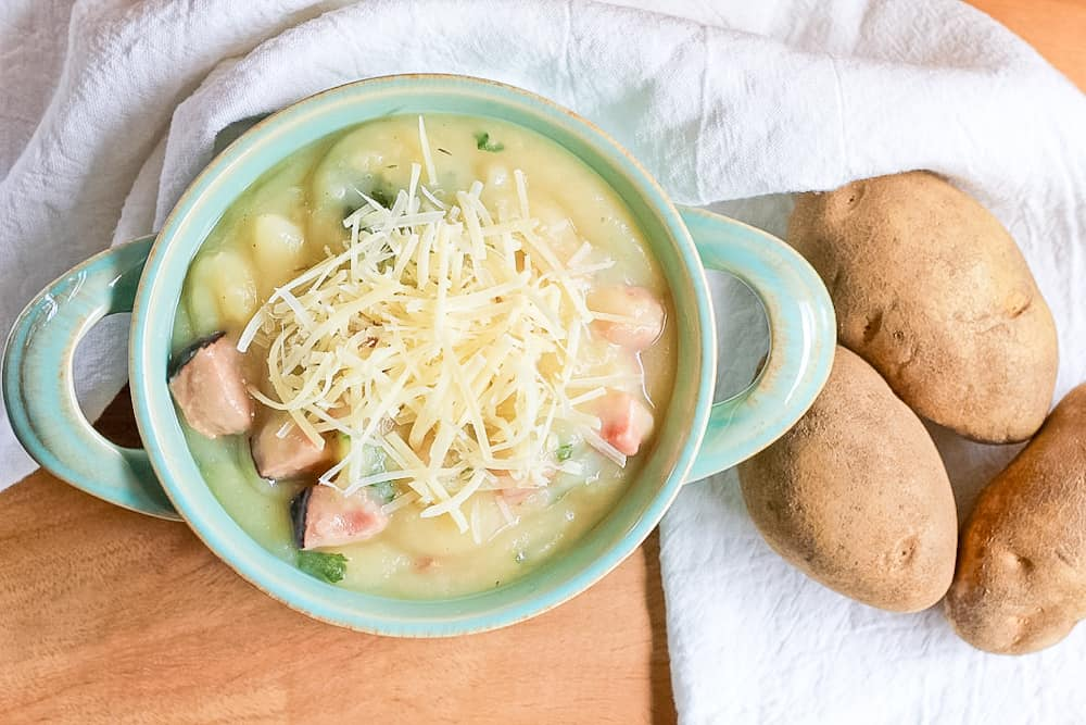 Bowl of Instant Pot Creamy Potato Ham & Kale Soup with russet potatoes.