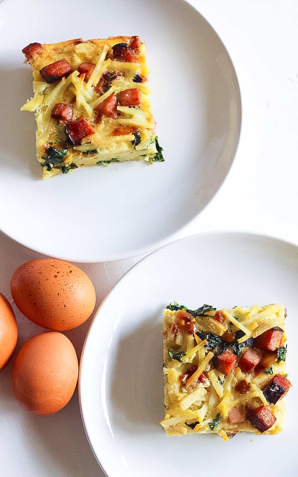 Paleo Ham and Egg Breakfast Bake on white plates with eggs
