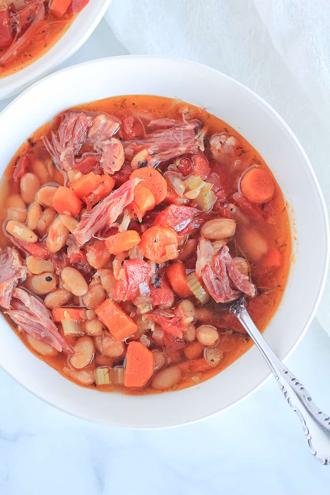 Close up view of Instant Pot Ham and Bean Soup served in a white bowl.