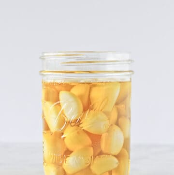 How to Preserve Garlic in a pint mason jar filled with garlic cloves and oil.
