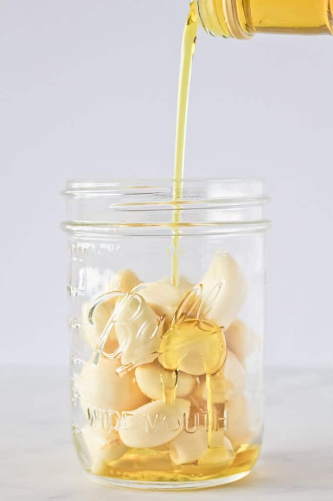 Oil being poured into a mason jar over garlic cloves.