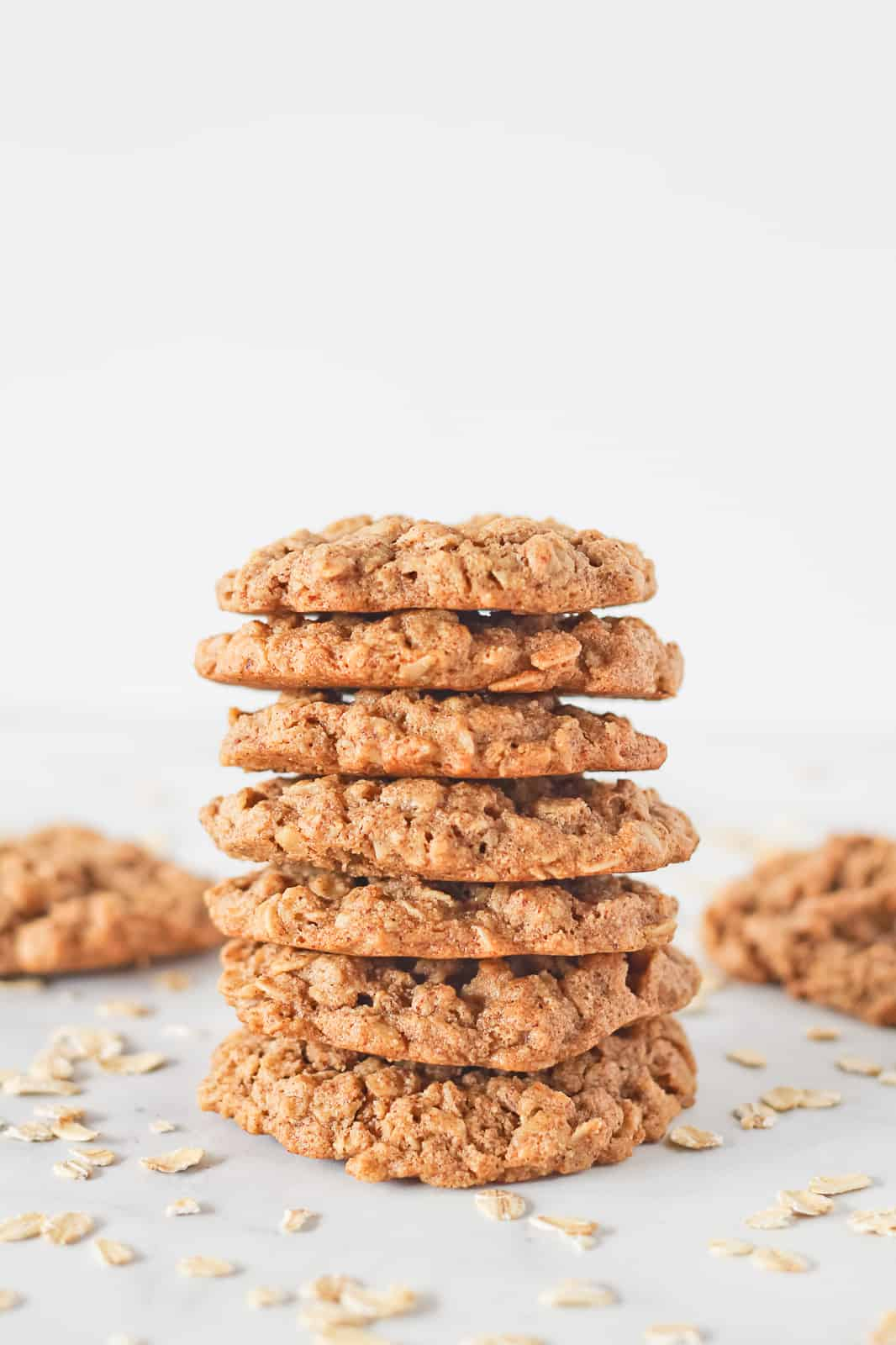 Vegan Oatmeal Cookies in a stack of seven surrounded by more cookies and dry oats.