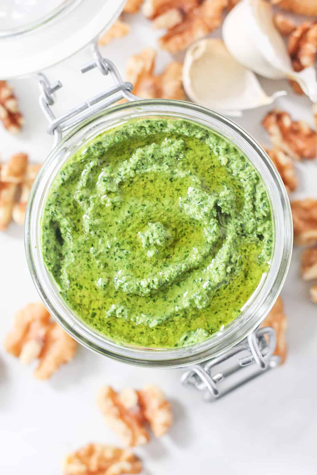 Rocket pesto in a glass jar drizzled with olive oil.