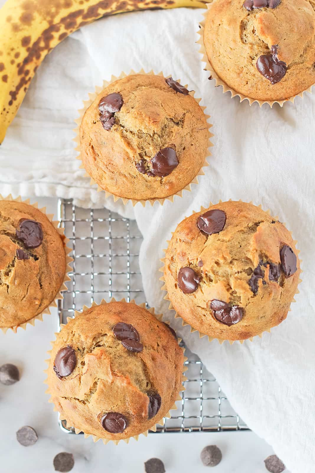 Gluten Free Dairy Free Banana Chocolate Chip Muffins on a cooling rack with white towel.