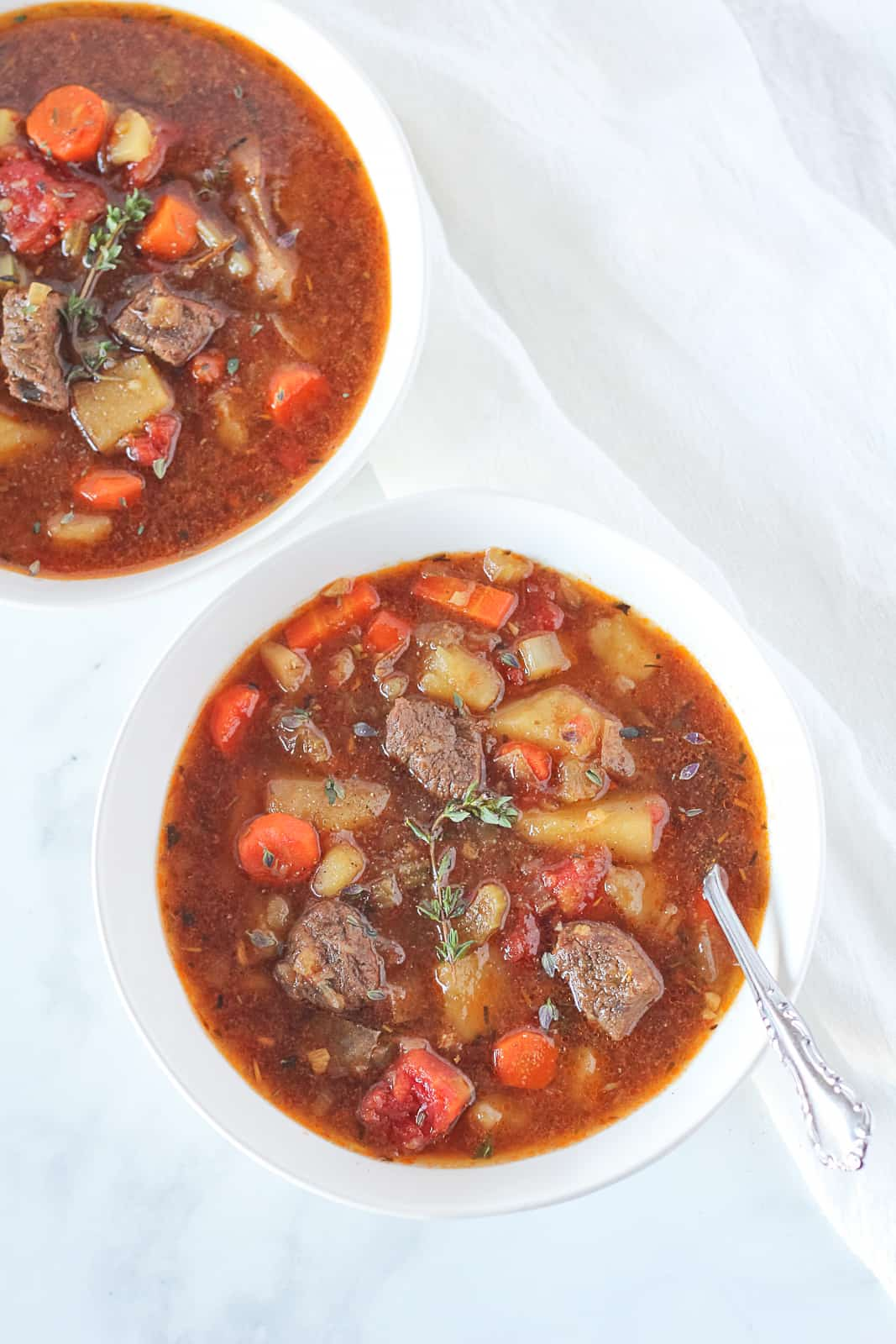 Venison stew in two white bowls with a spoon in one bowl.