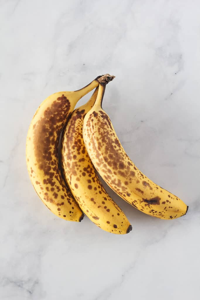 Three ripe bananas in the peel with black spots.