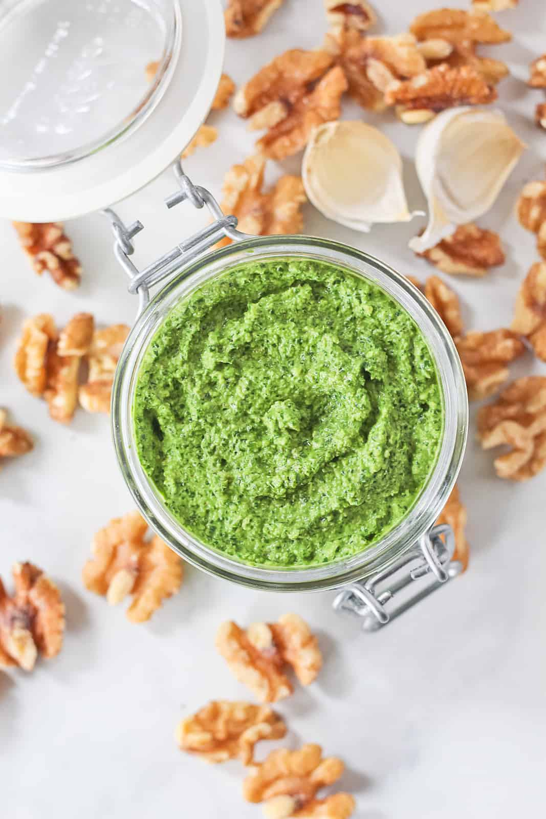 Arugula Pesto in a small glass jar surrounded by walnuts and garlic.