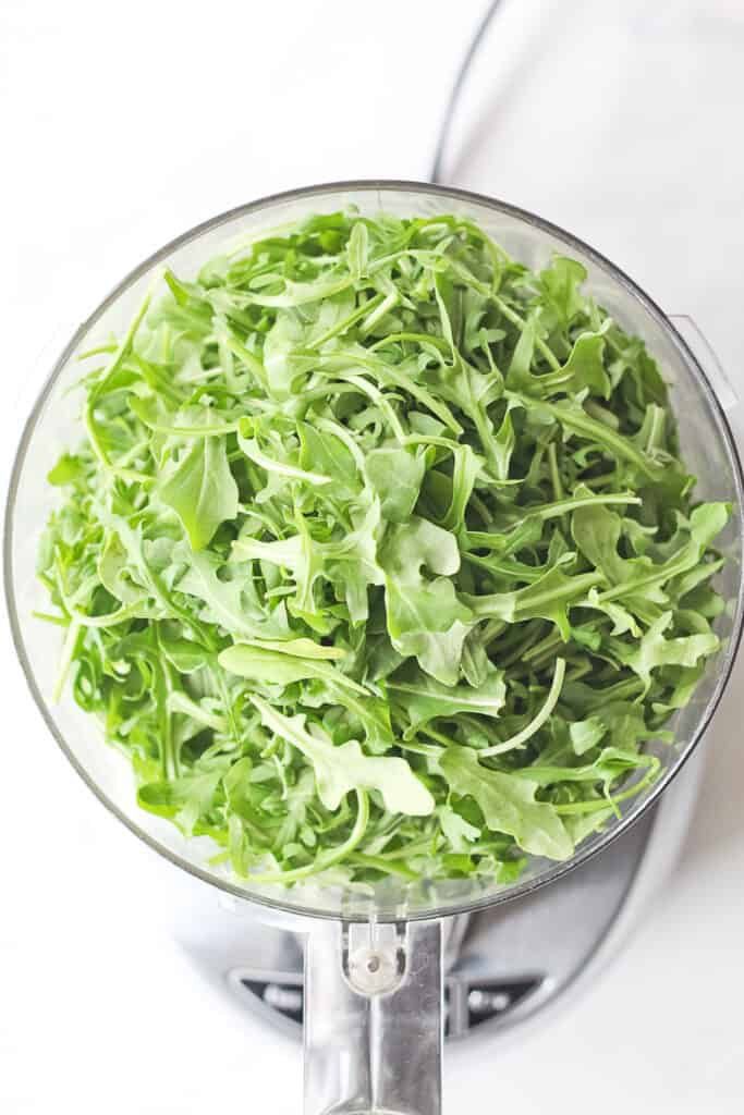 Food processor full of arugula.