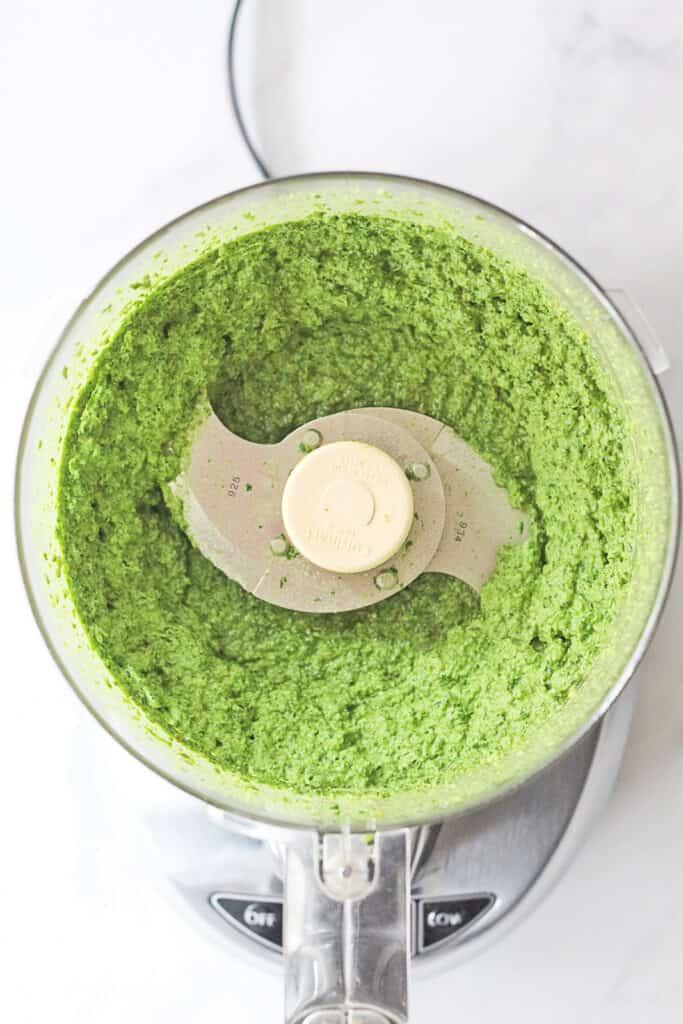 View of pesto being made in a food processor.