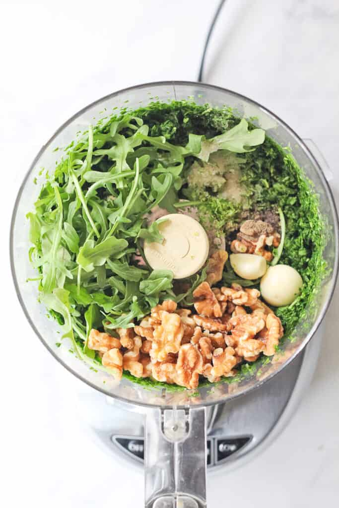 Food processor full of pesto ingredients.