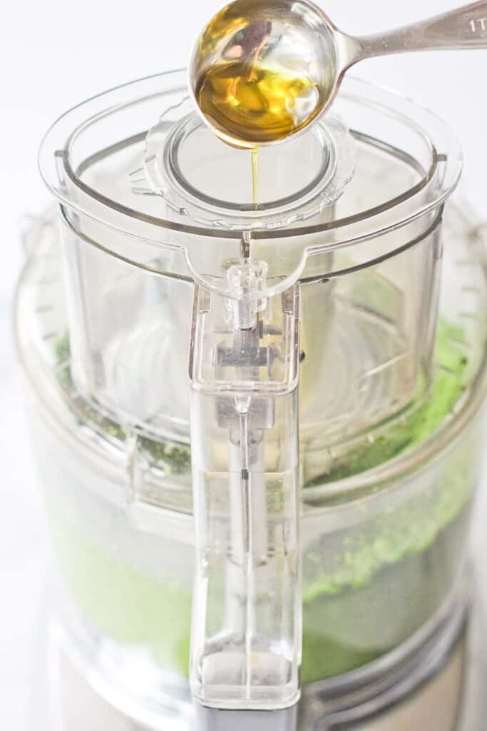Olive oil being drizzled into a food processor.