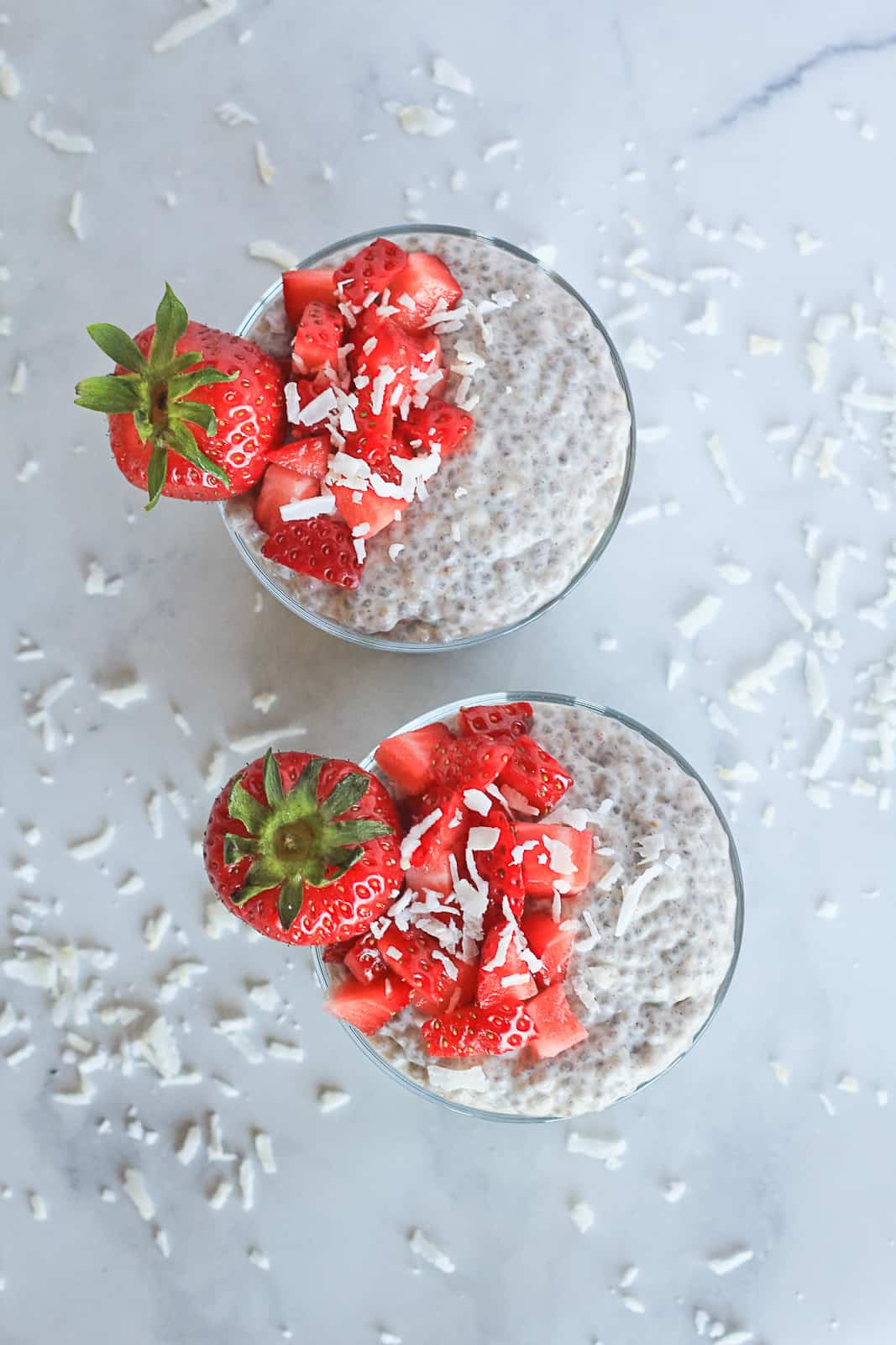 Top view of two jars with chia seed pudding, strawberries and coconut flakes.