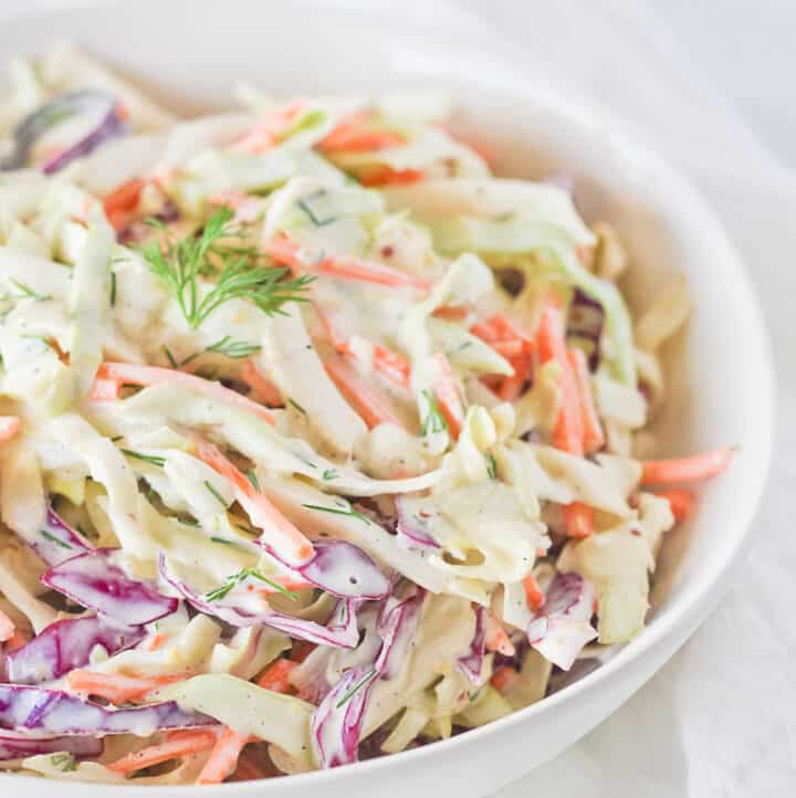 Whole30 Coleslaw with homemade dressing in a white bowl.