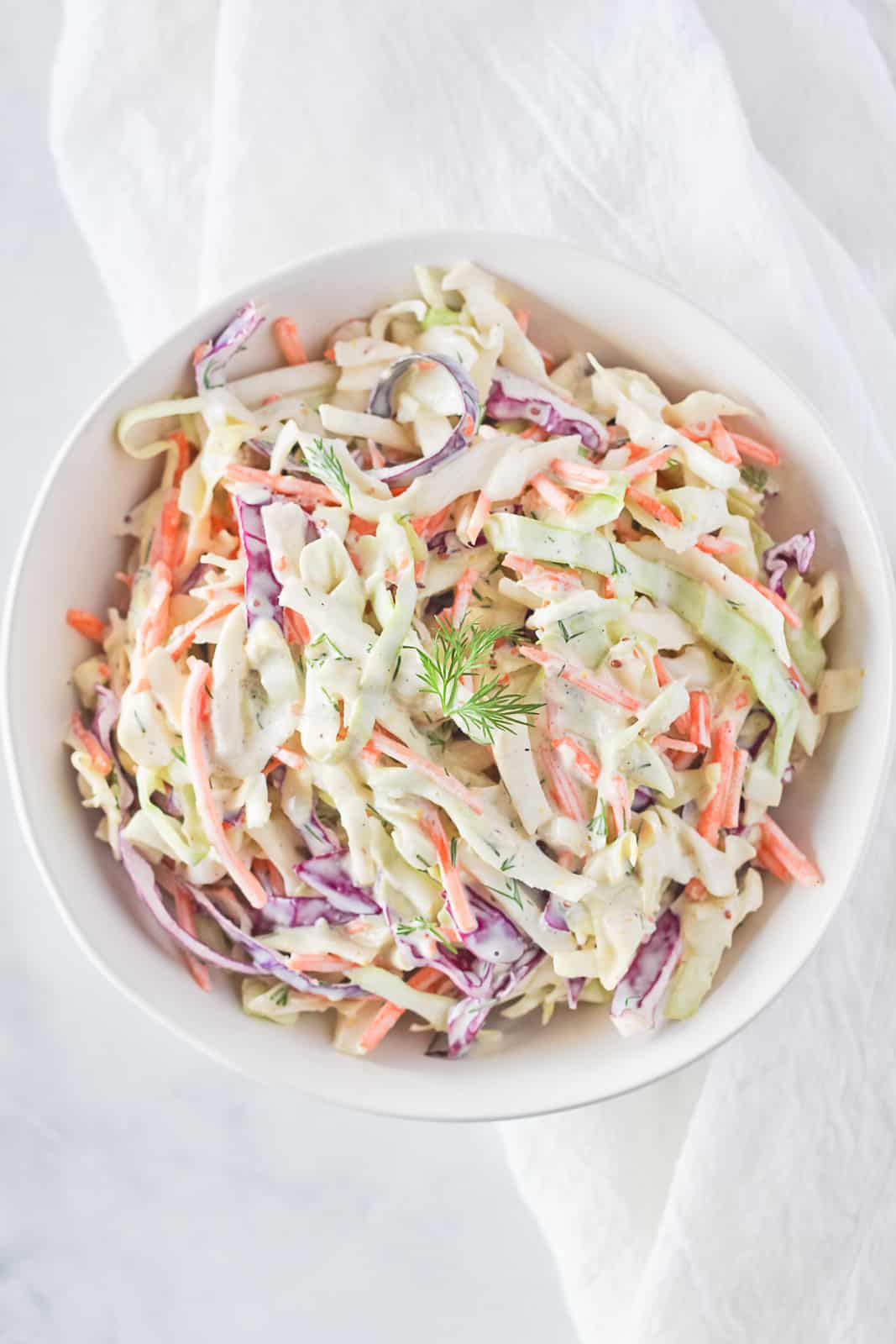 White serving bowl of shredded cabbage and carrot salad.