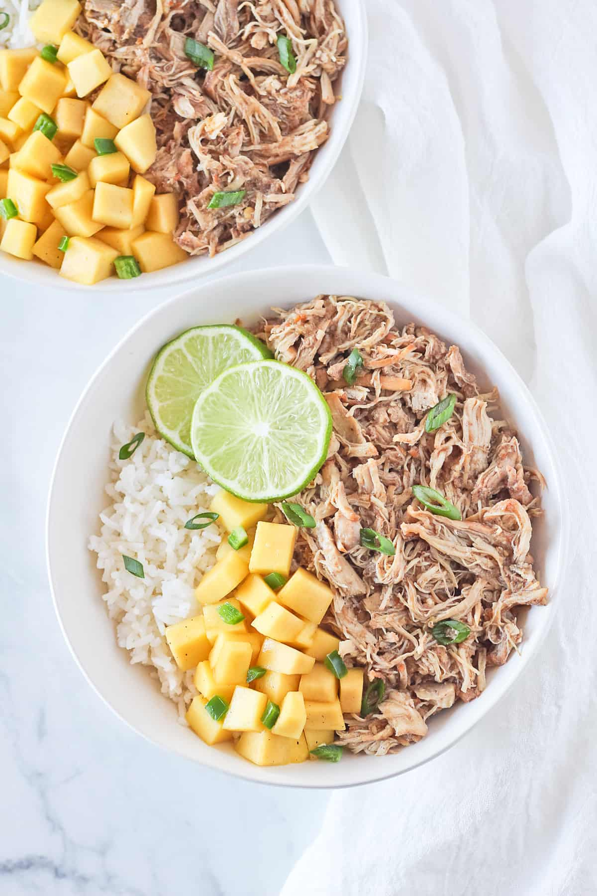 Two white bowls of rice, jerk chicken, mango, jalapeno, green onion and lime slices.
