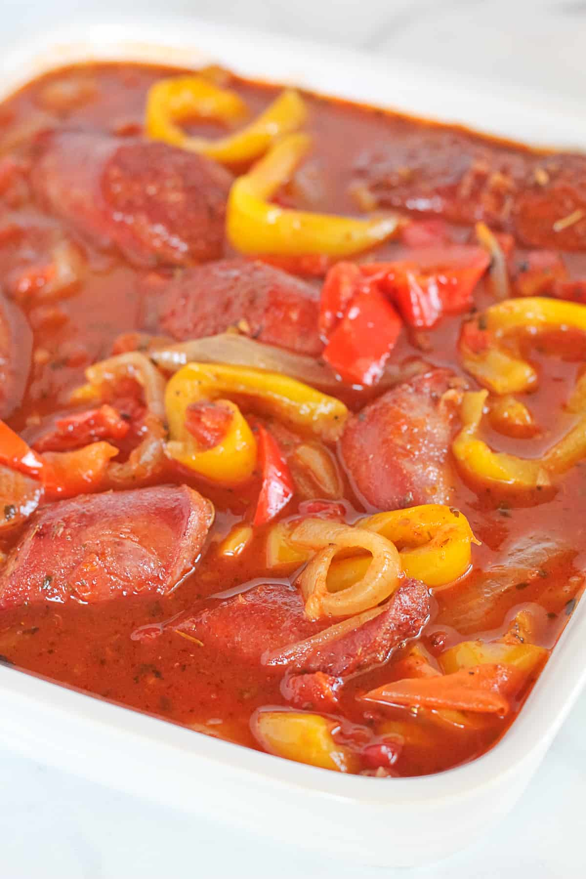 Sausage, peppers and onions in a white dish.