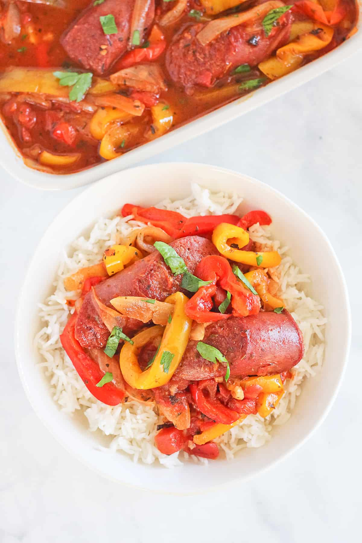 Sausage and peppers over white rice topped with fresh parsely.