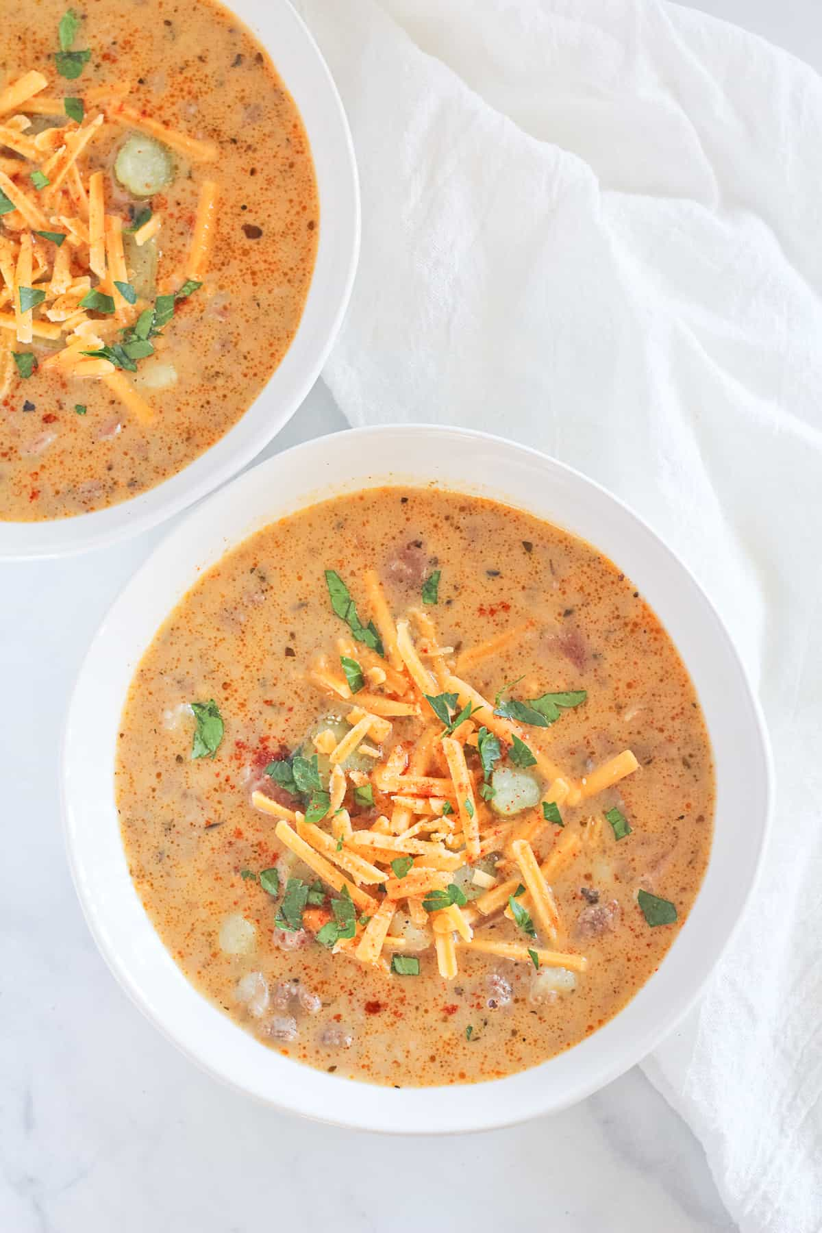 Cheeseburger soup in white bowls topping with cheese, pickles and smoked paprika.