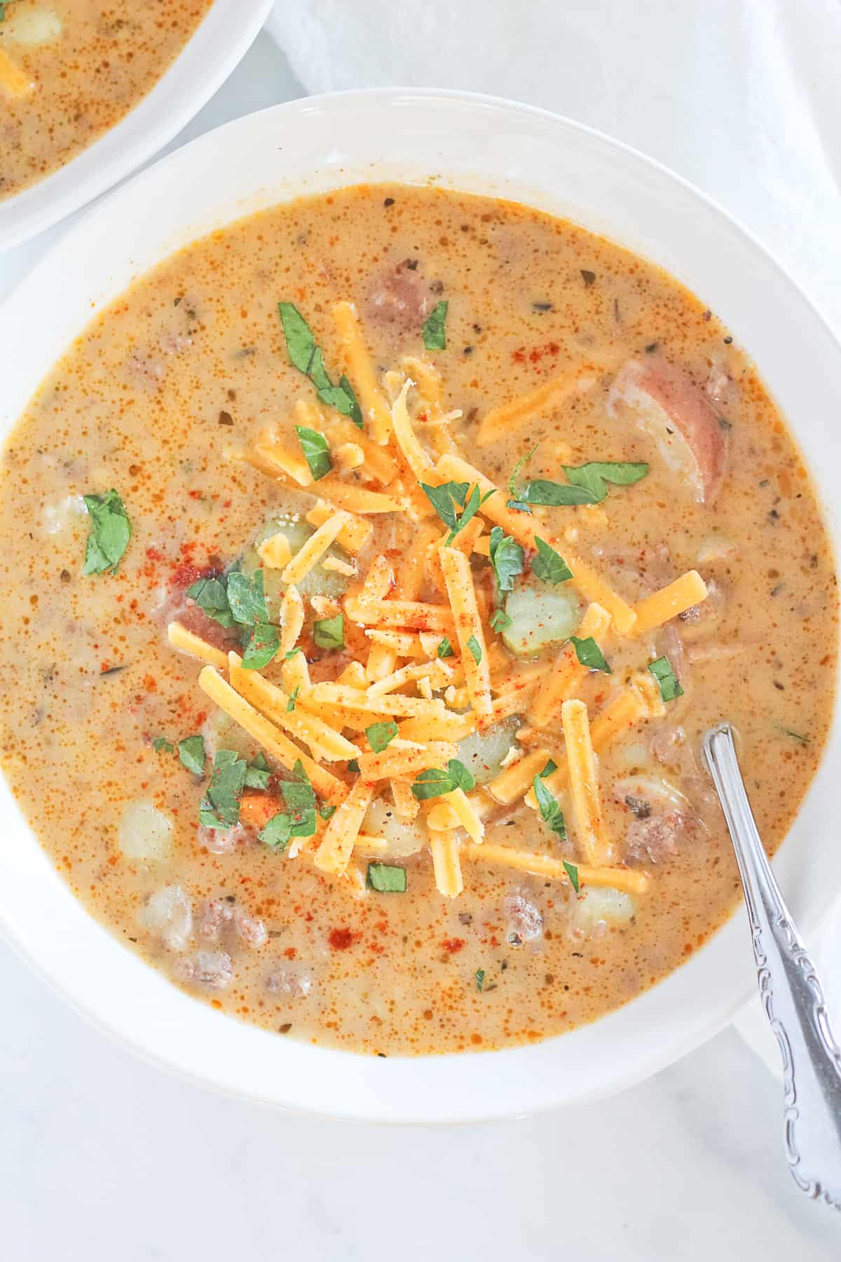 Large bowl of cheeseburger soup topped with cheddar, parsley and dill pickles.