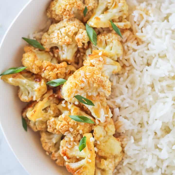 Vegan cauliflower orange chicken in a white bowl with basmati rice, green onions and sesame seeds.