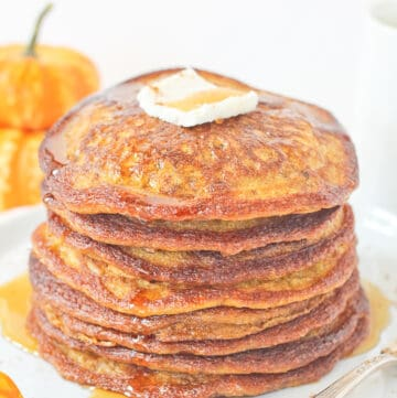 Stack of pumpkin sourdough starter pancakes with maple syrup and butter.